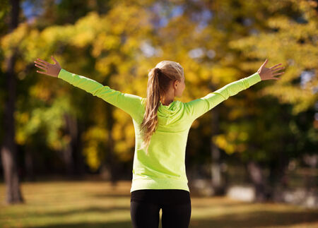 sport, fitness, exercise and lifestyle concept - woman doing sports outdoors Stock Photo