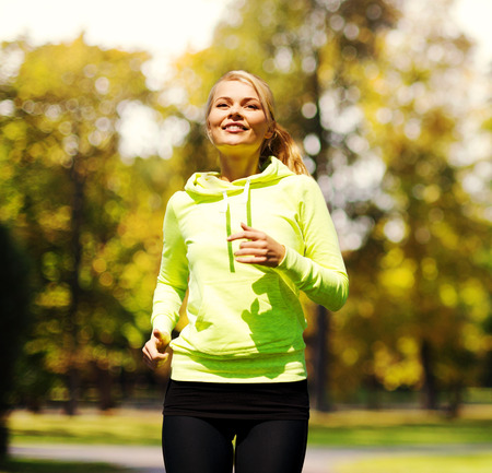fitness and lifestyle concept - female runner jogging outdoors photo