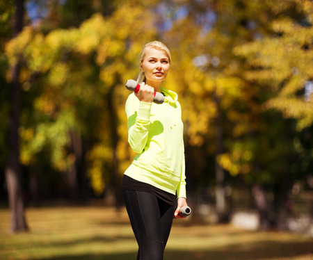 sport and lifestyle concept - young sporty woman with light dumbbells outdoors photo