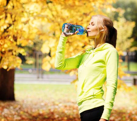 la escucha activa: fitness y estilo de vida concepto - mujer de agua potable después de hacer deportes al aire libre