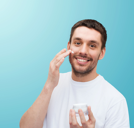 health and beauty concept - beautiful smiling man with jar of cream applying cream photo