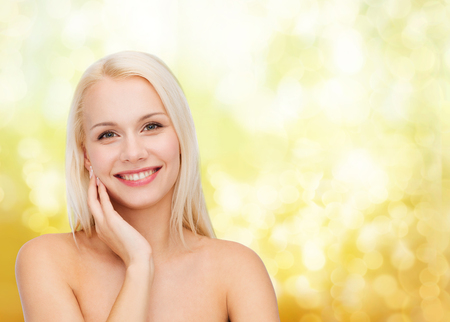 model nice: health and beauty concept - smiling young woman touching her face skin