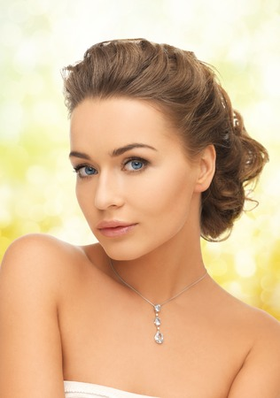 beauty and jewelry concept - woman wearing shiny diamond pendant photo