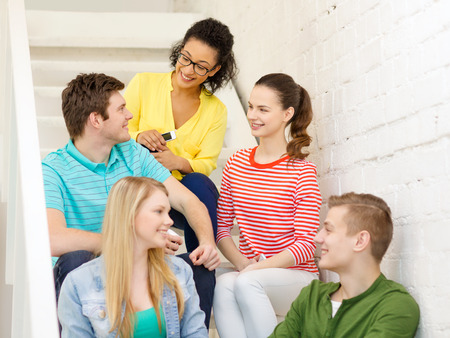 education, school and technology concept - smiling students with smartphone having discussion at school photo