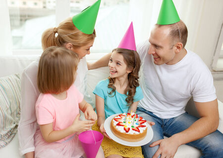 celebration, family, holidays and birthday concept - happy family with two kids in hats with cake at home photo