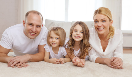family, children and home concept - smiling family with and two little girls lying on floor at home photo