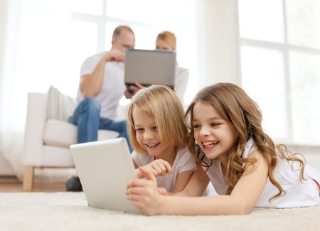 watching movie: family, children, technology and home concept - smiling sister with tablet pc computer and parents on the back with laptop