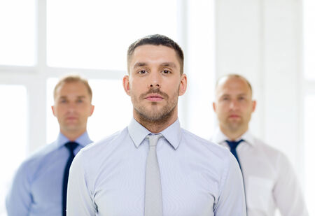 business and office concept - serious businessman in office with team on the back photo