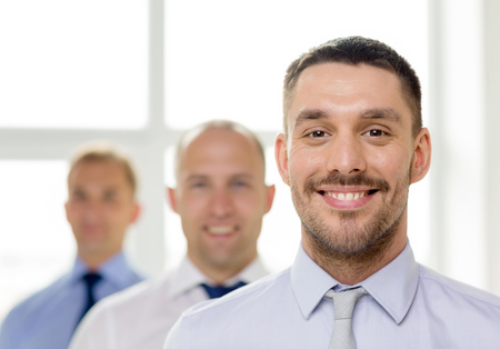 business and office concept - smiling businessman in office with team on the back photo