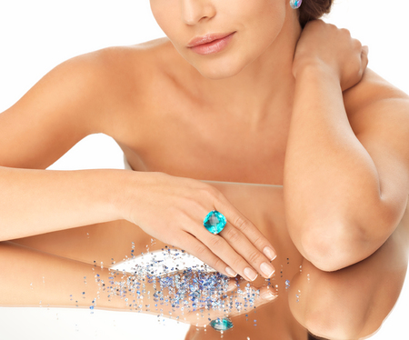 wedding, bridal jewelry and luxury concept - beautiful woman with big blue cocktail ring and shiny crystals on mirror photo
