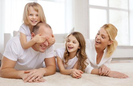 haciendo el amor: la familia, los niños y concepto de hogar - sonriendo familia con dos niñas pequeñas y acostado en el piso en casa y que se divierten