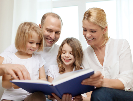 family, child and home concept - smiling family and two little girls with book at home photo