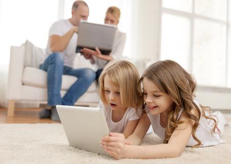 familia, los niños, la tecnología y el concepto de casa - hermana sonriente con la tablilla del ordenador pc y los padres en la parte posterior con el ordenador portátil