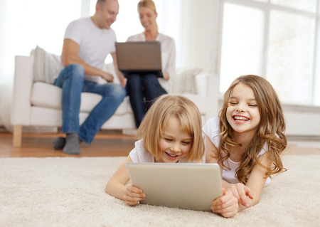 kids playing video games: family, children, technology and home concept - smiling sister with tablet pc computer and parents on the back with laptop