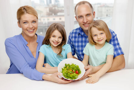 food, family, children, happiness and people concept - happy family with two kids with salad at home photo
