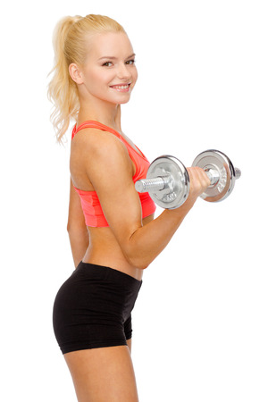 fitness, healthcare and exercise concept - young sporty woman with heavy steel dumbbell photo