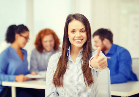 business, office and startup concept - smiling young businesswoman showing thumbs up photo