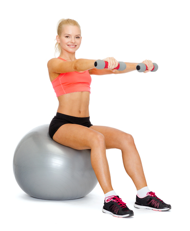 fitness, exercise and diet concept - smiling sporty woman with dumbbells sitting on fitness ball photo