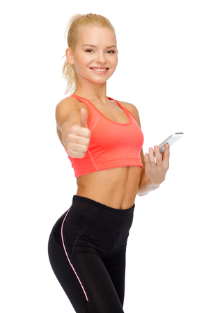 sport, fitness, technology, internet and healthcare - smiling sporty woman with smartphone showing thumbs up photo