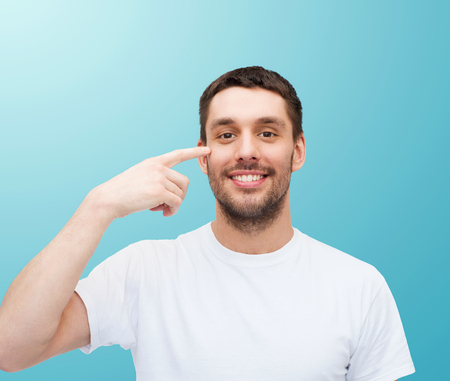 health and beauty concept - smiling young handsome man pointing to eyes photo