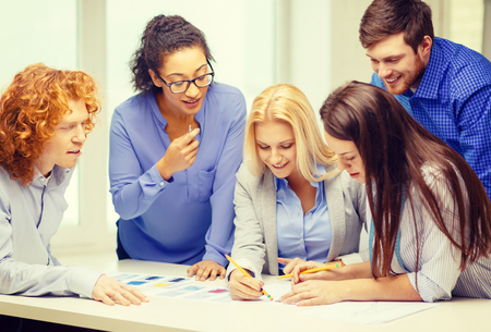 business, office, clothes design and starup concept - smiling creative team looking over clothes designs photo