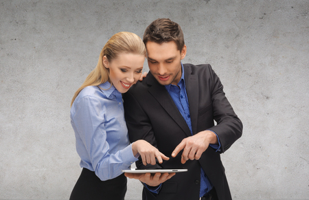 business, technology and office concept - smiling businesswoman and businessman looking at tablet pc computer photo