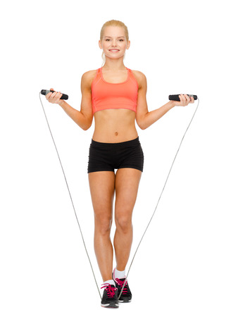 woman rope: sport, excercise and healthcare - smiling sporty woman with skipping rope