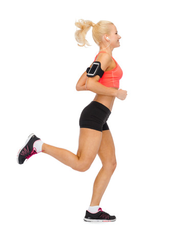 sport, exercise, technology, internet and healthcare - smiling sporty woman running and listening to music from smartphone photo