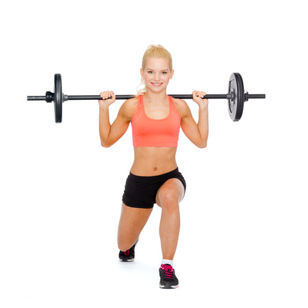 fitness, sport and exercise concept - smiling sporty woman with barbell doing split squat or lunge photo