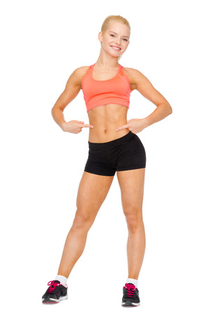 fitness, exercise and diet concept - smiling beautiful sporty woman pointing at her six pack photo
