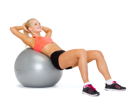fitness, exercise and diet concept - smiling sporty woman exercising on fitness ball photo