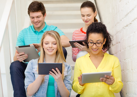 education and technology concept - smiling students with tablet pc computer sitting on staircase photo