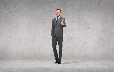 business, gesture and office concept - handsome businessman showing thumbs up photo
