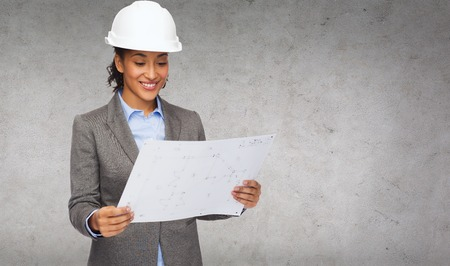 building, developing, construction and architecture concept - smiling businesswoman in white helmet looking at blueprint photo