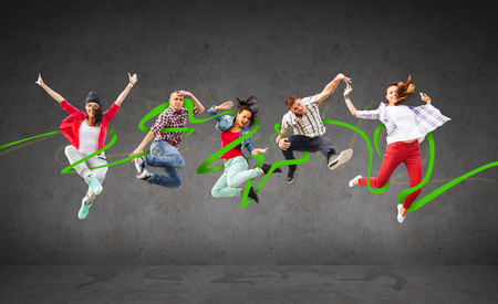 funky music: summer, sport, dancing and teenage lifestyle concept - group of teenagers jumping Stock Photo