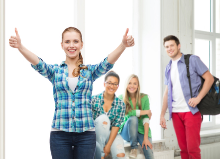 happiness and people concept - smiling girl in casual clothes showing thumbs up photo