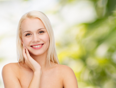 sensitive skin: health and beauty concept - smiling young woman touching her face skin