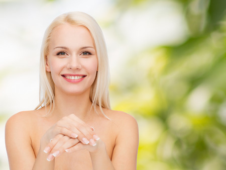 health and beauty concept - face and hands of beautiful woman Stock Photo