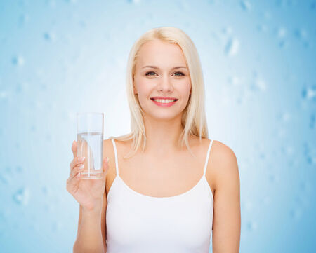 health and beauty concept - young smiling woman with glass of water photo