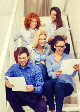 business, office and startup concept - smiling creative team with papers and take away coffee on staircase photo