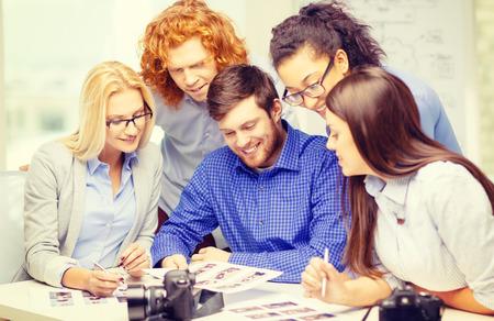 bedrijf, kantoor en startup concept - lachende creatief team met fotos en beelden werken in kantoor Stockfoto