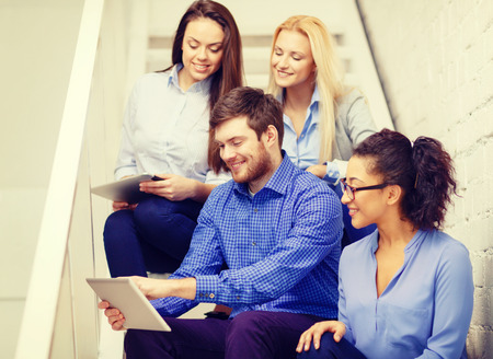 business, technology and startup concept - smiling creative team with tablet pc computer sitting on staircase photo