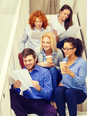develope: business, office and startup concept - smiling creative team with papers and take away coffee on staircase Stock Photo