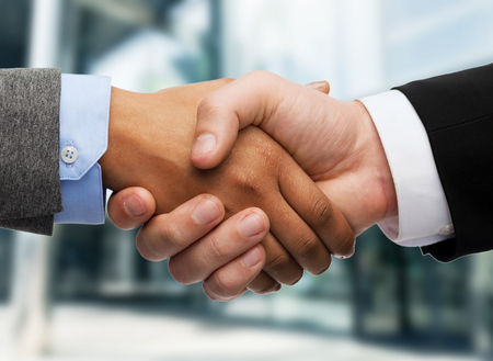 business and office concept - businessman and businesswoman shaking hands outdoors photo