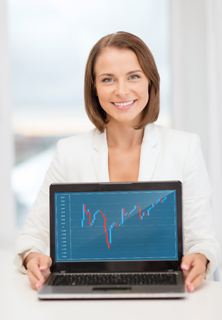 education, business, technology and internet concept - smiling woman with laptop computer in office showing forex chart photo