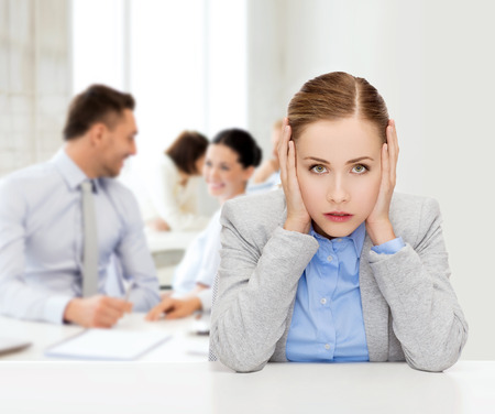 depressed person: business and office concept - stressed businesswoman covering her ears with hands Stock Photo