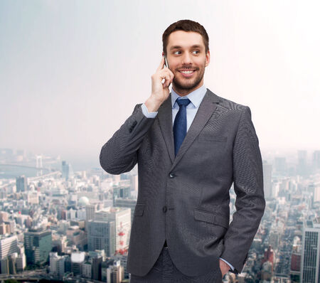 business, technology and education concept - friendly young smiling businessman with smartphone photo