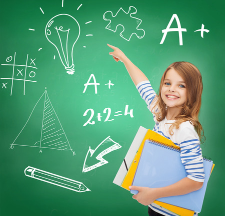 education, school and virtual screen concept - cute little girl with colorful folders pointing to green board photo