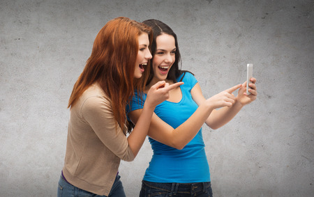 technology, friendship and people concept - two smiling teenagers pointing finger at smartphone photo
