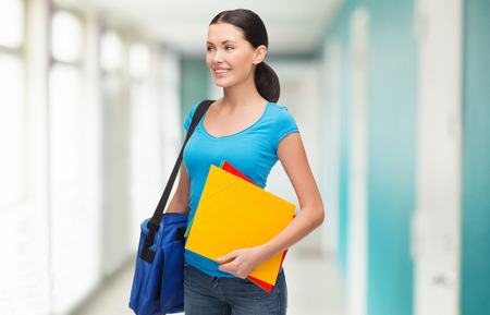 education and people concept - smiling female student with bag and folders photo
